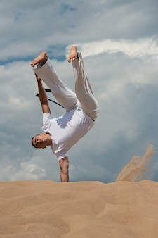 A young guy trains capoeira against the sky. a man performs an acrobatic trick
