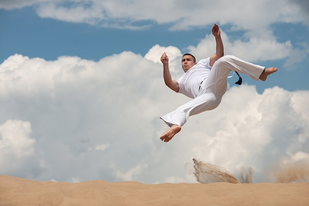 Young guy trains capoeira on sky backround. a men performs martial the kick in the jump