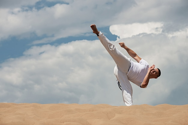 Young guy trains capoeira on sky backround. a men performs martial the kick