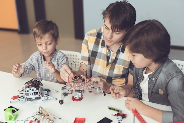A young guy and two little boys are collecting robots.