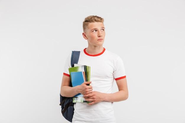 Молодой парень, студент университета или колледжа, носящий рюкзак, глядя в сторону на copyspace, держа учебники, изолированные на белом