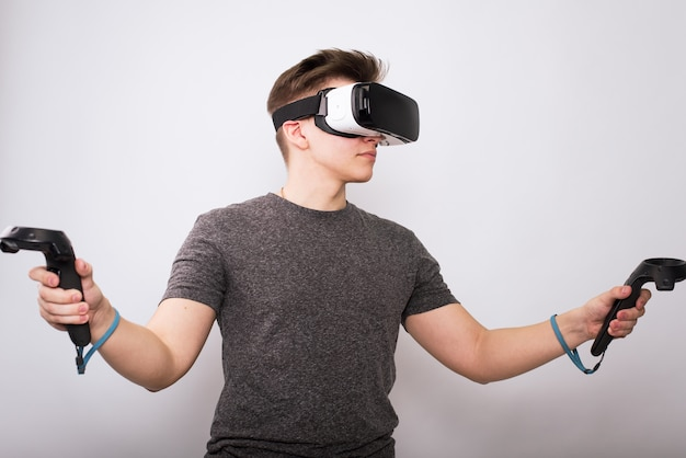 Young guy in viar glasses. a teenager plays with virtual reality glasses and considers joysticks and gamepads