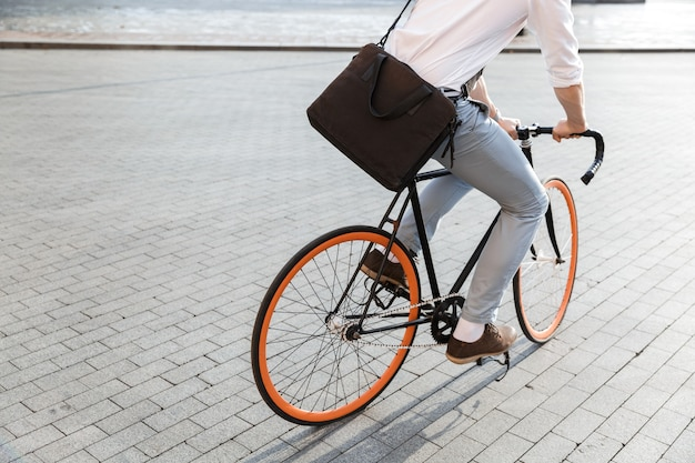 공식적인 옷을 입고 도시 거리에서 자전거를 타는 젊은 남자