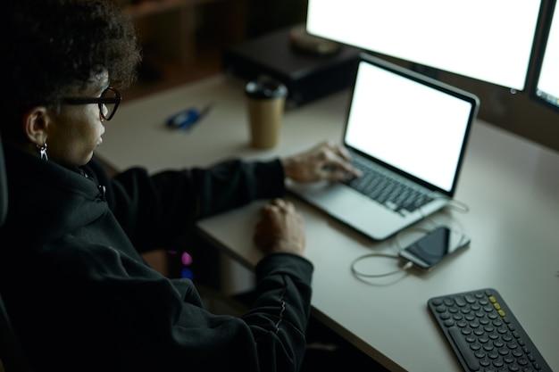 多くのコンピューターモニターの前のテーブルに座って、ラップトップを使用して眼鏡をかけている若い男