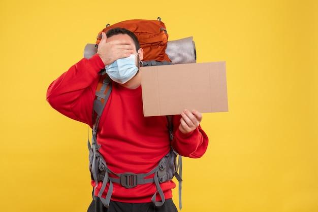 バックパックで医療用マスクを着用し、孤立した黄色の背景に目を置かずにシートを保持している若い男