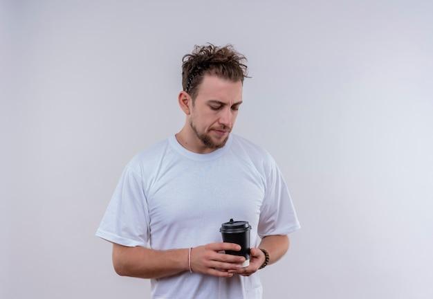 孤立した白い壁に彼の手でコーヒーのカップを見て白いtシャツを着て若い男