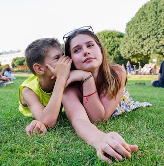 Молодой парень шепчет на ухо девушке на зеленой лужайке.