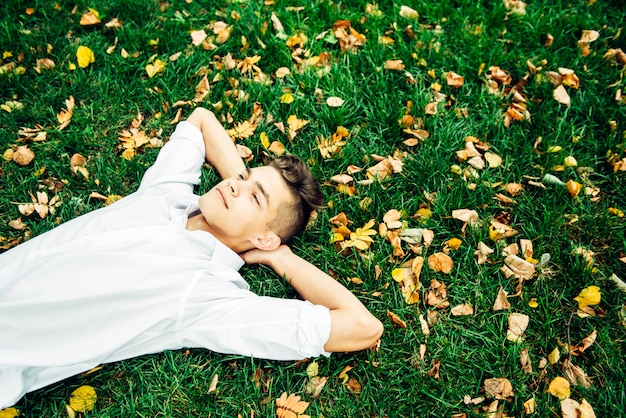 A young guy in a white shirt lies on the grass with autumn leaves