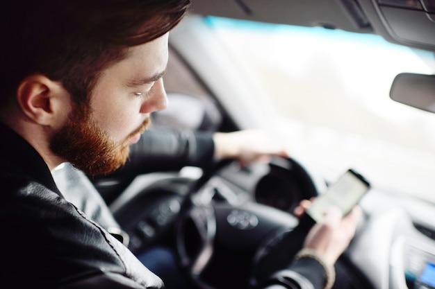 あごひげを生やした若い男が車の中でスマートフォンにメッセージをダイヤルします