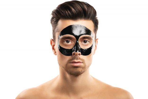 白の顔に黒い炭マスクを持つ若い男。