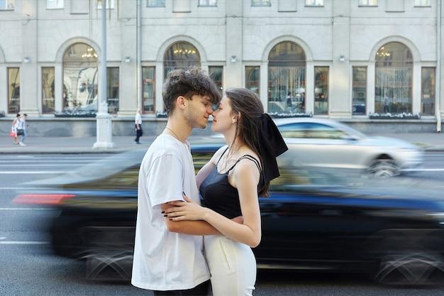 街で夏に抱き締める女の子と若い男。後ろから背景に動いている車がぼやけている道路が見えます。