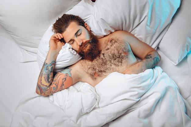 長い口ひげとあごひげを生やした若い男が白いベッドに横たわって寝ています。
