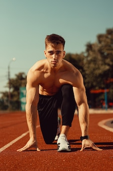 Young guy with athletic body getting ready to run