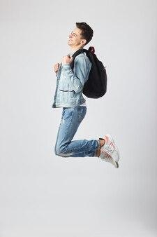 배낭을 메고 스튜디오의 흰색 배경에 점프하는 젊은 남자