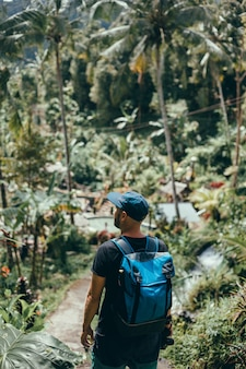 Young guy with a beard and a backpack posing in the jungle in a cap