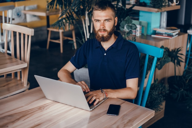Young guy with a beard works in a cafe, freelancer uses a laptop, does a project