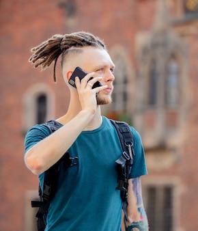 Молодой парень с дредами разговаривает по телефону на городской улице