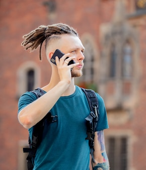 Young guy with dreadlocks is talking on the phone on city street