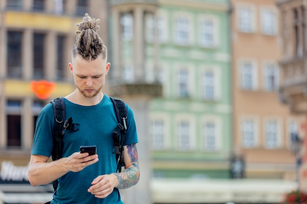 Young guy with dreadlocks is walking with a phone on the street