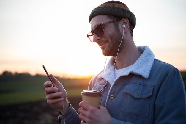 Молодой парень с наушниками делает селфи на смартфоне с чашкой кофе в руке