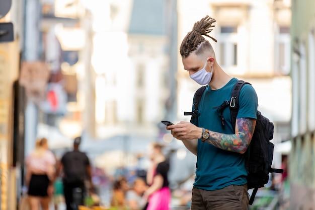 Молодой парень в маске и дредах пользуется мобильным телефоном на улице