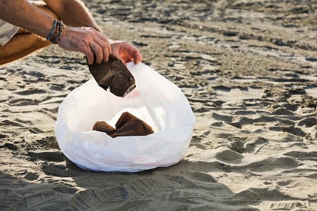 ビーチの屋内でゴミ袋とさびた缶を持つ若い男