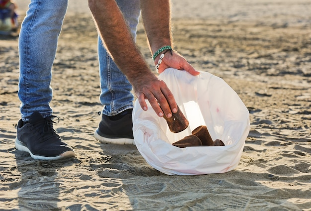 Young guy with garbage bag and rusty cans indoors on the beach
