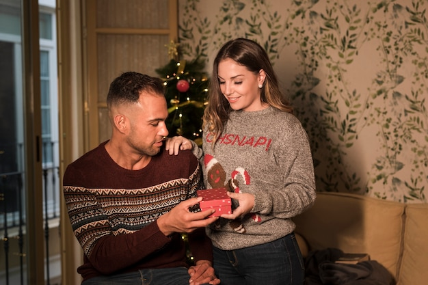Young guy with gift box and cheerful lady on settee near christmas tree