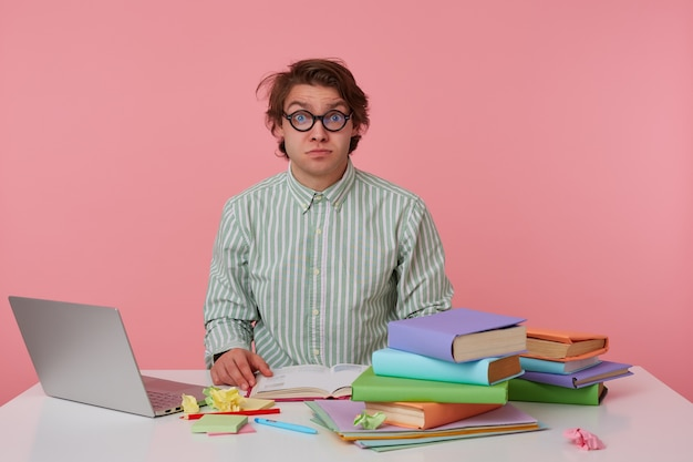 Young guy with glasses, wears on blank shirt, sitting at a table with books, working at a laptop, looks shocked and confused. isolated over pink background.