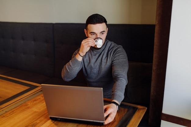 彼の携帯電話とコーヒーを持っている若い男。昼食時にシティカフェで若いファッションの男性エスプレッソコーヒーとラップトップコンピューターで作業