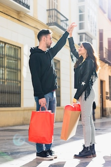 Young guy with packets holding upping hand of happy lady on street