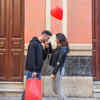 Young guy with packets kissing hand of lady and flying balloon