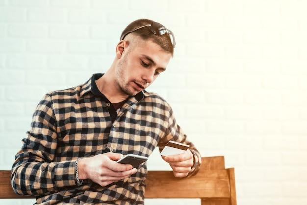 Молодой парень с телефоном и кредитной картой на скамейке
