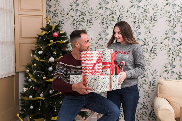 Young guy with pile of gifts and attractive lady near christmas tree
