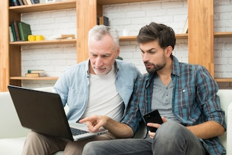 Young guy with smartphone pointing at monitor of laptop on legs of aged man on sofa