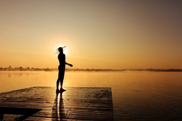 Молодой парень с сильными мышцами стоит на деревянном пирсе