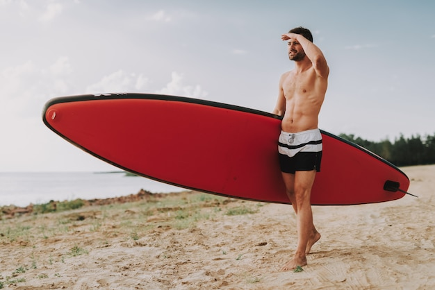 Young guy with surf standing on beach.