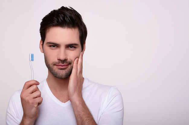 A young guy with a toothache holds a toothbrush in his hand.