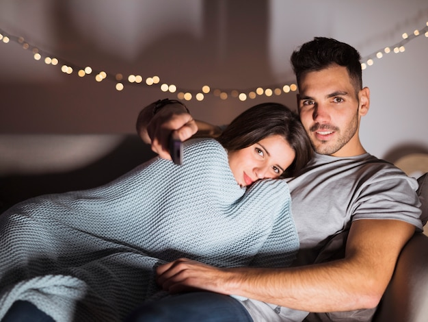 Young guy with tv remote hugging lady and lying on sofa