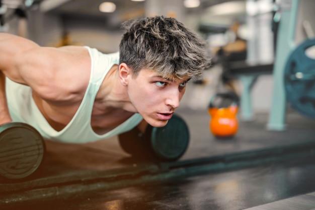 Молодой парень тренируется в тренажерном зале