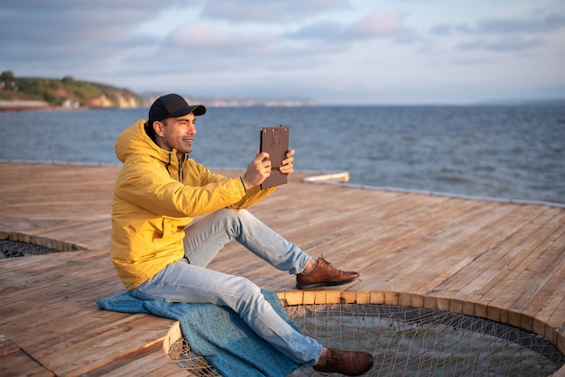 Young guy in a yellow windbreaker, black cap sitting on a wooden pier, takes a photo of sunrise on the tablet