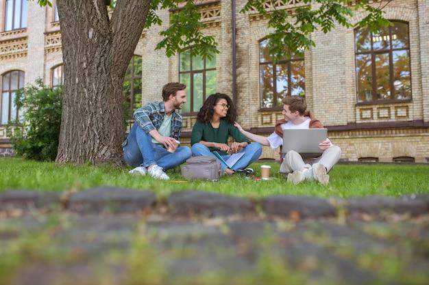 젊은 남자와 여자는 대학 건물 근처 잔디에 앉아