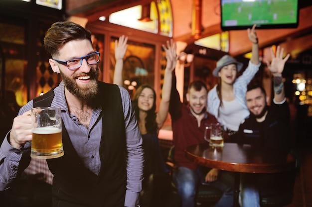 Молодые парни и девушки держат бокалы с пивом, смотрят футбол, смеются и улыбаются