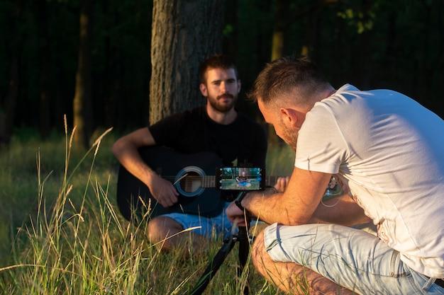 若い男たちはビデオで演奏しているギターを録音しています。
