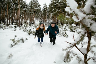 Young guys having fun in the forest in snowy winter weather.