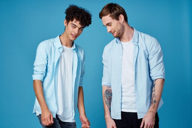 お揃いのtシャツとtシャツを着た若い男性がポーズをとる