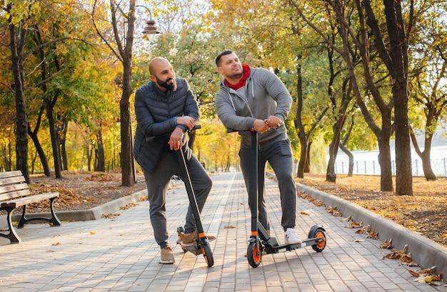 Молодые парни катаются в парке на электросамокате теплым осенним днем