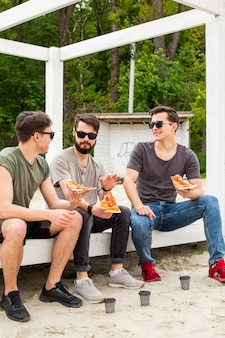 Young guys talking while holding pizza on rest