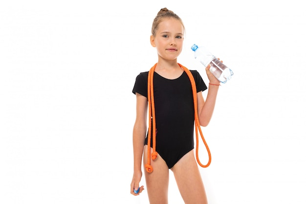 Young gymnast champion in sportswear holds a water bottle with a mock-up on a white background with copy space