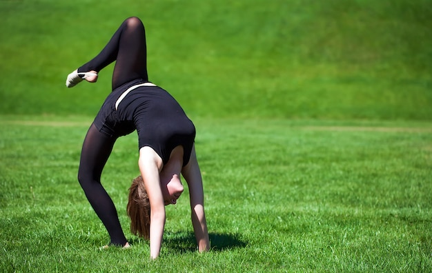 Young gymnast on grass in sunny day